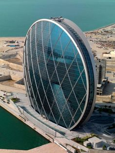 Aldar headquarters building in Abu Dhabi. Designed by MZ Architects and opened in This coin-shaped building is the world's first circular skyscraper. Circular Buildings, Unusual Buildings, Amazing Buildings, Modern Buildings, Office Buildings, Modern Houses, Futuristic Architecture, Beautiful Architecture, Architecture Design
