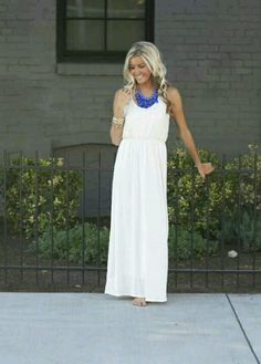 Long white dress with blue neclace.