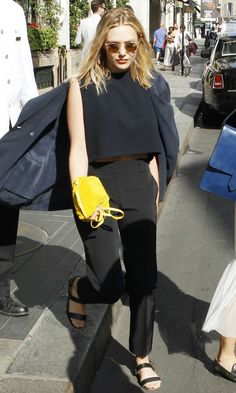 Elizabeth Olsen in all black with double strap sandals + a bright yellow clutch.