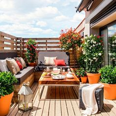 Terraza pequeña en madera con bancos con base de madera y cojines de asiento y respaldo grises, mesa de centro, farolillo, puf con plaid y plantas