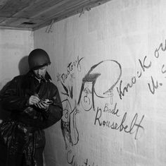 An American soldier leans against a wall in the captured Japanese headquarters on Kiska Island, beside graffiti caricatures of FDR and Churchill (left), 1943