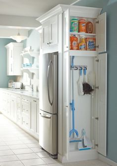 Muebles de una cocina con un pequeño gabinete al costado del refrigerador para guardar los productos de limpieza