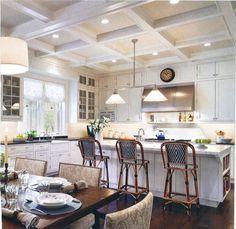White kitchen med-dark wood floor, counters black, island white