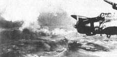 B5N2 Кага летит над авиабазе Hickam  Эта фотография показывает линкоров в фоновом режиме (на фото в центре) , горящий и авиабаза Hickam на фото  прямо горит слишком , В B5N2 стеллажи перевезти 800 кг бомбу четко видны.