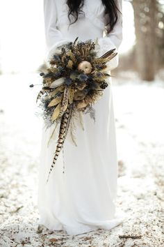 Gold and blue rustic winter wedding bouquet. LOVE the idea of putting feathers in a rustic wedding bouquet! Bouquet En Cascade, Feather Bouquet, Thistle Bouquet, Feather Boutonniere, Dried Flower Bouquet, Flower Bouquets, Boutonnieres, Winter Wedding Flowers, Autumn Wedding