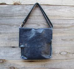 Measurements: 12 x 11 x 1.5 inches  Materials: Distressed navy leather is 2 oz weight (light yet durable). Raw and rustic raw edge flap. This leather