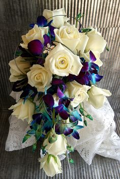 White roses and blue dendro orchids designed into a cascading wedding bouquet! Weddings should be a reflection of your personal style, and at H&J Florist we try to show what you love through flowers, texture, color, and style. Give us a call for all your floral needs, to speak with someone about a wedding please try to call at least a week in advance so we may be sure to have someone here to speak with you.  Give us a call at 269-429-3621.