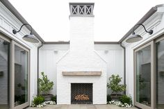 Two pairs of gray sliding glass doors, facing each other, open to reveal a chic patio finished with a white brick fireplace accented with a black herringbone firebox and lined with a rustic chunky fireplace mantle.