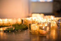 Floor votives with fern wreath.  Event design and rentals provided by Eclectic Hive