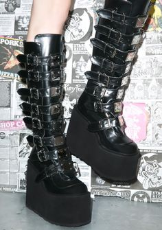 """Demonia Trinity Boots red pill or blue pill? That's the question when yer wearin' these bad af boots. Featurin' buckles all the way up yer leg and a killer 5 1/2"""" platform these shoes will def let you enter the Matrix.."""