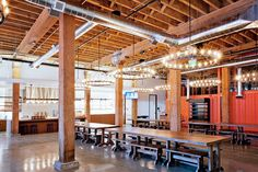 Github's picnic table style benches with chandeliers overhead give the kitchen office space a feeling of importance.