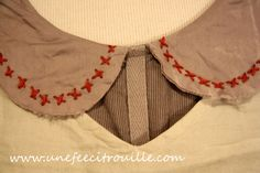 Cross stitches in red, on a grey peter pan collar