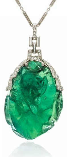 An Art Deco Platinum, Fluorite and Diamond Pendant, consisting of a carved fluorite pendant in a foliate motif with a platinum mounting containing six baguette cut diamonds weighing approximately 0.18 carat total and 86 single cut diamonds weighing approximately 0.86 carat total, suspended from a fancy link platinum chain.