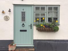 I love the colour of this front door,the old~fashioned doorbell & also the cute window box with daffodils growing in it.The name of it is B's cottage,just adorable! Cottage Style Front Doors, Green Front Doors, Cottage Door, Front Door Entrance, House Front Door, House Front Design, Cottage Exterior, Glass Front Door, Cottage Windows