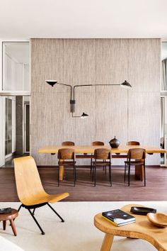 scandinaviancollectors:  The apartment of Emmanuel de Bayser in Berlin: Paul Frankl coffee table (1948), Charlotte Perriand stool (c.1950s), Jean Prouvé´s Antony-chair (1954) and Standard dining chairs (c.1950s). Wall sconce by Serge Mouille (c.1953-1954).