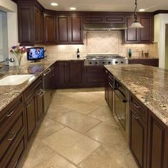 Dark kitchen cabinets, granite counter top, but with hardwood floors