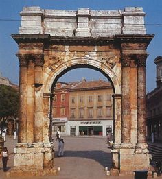 Arch of the Sergii, Pula, Croatia, c. 10-20 AD, limestone attic on top of sandstone the rest. Commissioned by Salvia Postuma Sergia, erected with her own money as on inscription on attic, honour deceased family members, statues stood on top. Not triumphal, victory over death, hence Victories in spandrels and eagle carrying snake skyward. Also Erotes, chariots, and bull skulls = funerary but triumphal over death.