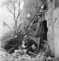 Wardens 'rescue' a young boy from the rubble and debris next to a bomb-damaged house in Fulham during a Civil Defence exercise in 1942.