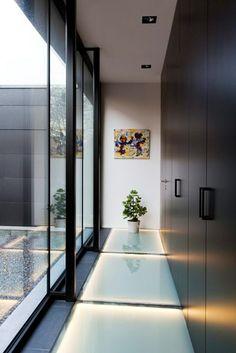 Glazen terras buiten en lichtstraat binnen schenken de kelder daglicht. Door een verhoging van het terras kreeg de kelder ook ramen op plafondhoogte voor nog meer licht.