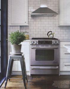 Tolix Stool as plant stand; kitchen w/ white subway tile