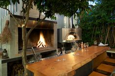 Outdoor kitchen w/ brick oven and cherry wood slab bar at Saison, SF