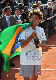 Guga comemora o título de Roland Garros com uma garrafa de champanhe e usando camisa com uma declaração de amor ao Grand Slam francês após o...