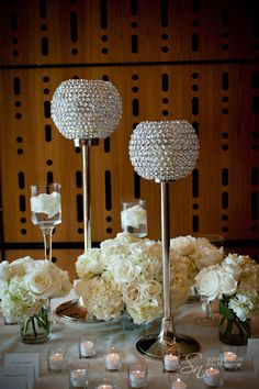 Crystal globes and white flowers. Create highs and lows with crystal globes and stemmed candle holders.