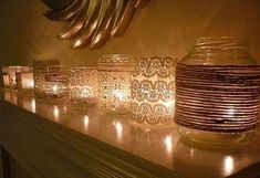 Jars covered in twine, lace and other materials with candles in the bottom.  Really nice for mantle during holiday