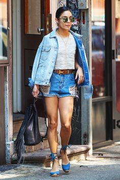 Vanessa Hudgens wears a gray crop top, belted denim cutoffs, a denim jacket, espadrilles, round sunglasses, gold necklaces, and a fringe backpack