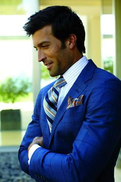 Mens street style fashion: bright blue checkered tweed suit with blue white striped shirt, orange blue white striped tie