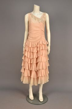 SILK EVENING DRESS with RHINESTONES, 1920s. / Sleeveless pale pink crepe decorated at asymmetrical neckline with prong set rhinestones, off center ruching to bodice, scalloped dropped waist and skirt layered with ruffles.