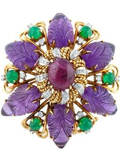 Carved Amethyst brooch with cabochon Ruby center accented by Diamonds and Emeralds. Set in 14k Gold. Circa 1970s