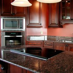 <p>In an otherwise very light and bright kitchen, dark cabinets can act as a dramatic anchor--and will show less wear and tear over time. �</p><p>Choose a paint or stain color that will complement your wall and tile back splashes. Ebony and espresso are good dark wood stains that you can get for your cabinets, or consider a rich, somber paint.�</p><p>This learning takes you to another ebony/espresso color scheme, with much lighter accents, just to show you the breadth of what's possible.</p>