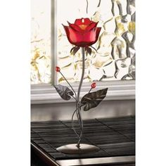 "Set the stage for an enchanted evening when you place a candle at the heart of this ruby-red rose! The timeless symbol of love is never lovelier than when filled with a candle's passionate flame.  	 Item Weight: 0.9 lb.  5"" x 4 1/8"" x 12 1/2"" high.  Iron, glass and acrylic.  Candle not included.  UPC: 849179002015."