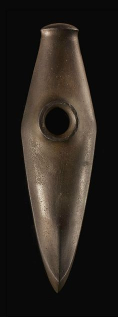 A NORDIC DARK BROWN STONE BATTLE AXE  NEOLITHIC PERIOD, CIRCA 2000-1700 B.C.  The surface polished, boat shaped, the convex sides swelling slightly around the shaft hole, with an oval convex butt, and a short curved cutting blade, the collared shaft hole with a flat rim, with two sets of two short striations incised on the underside on either side of the shaft hole 8 in. (20.3 cm.) long