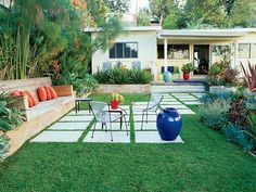 Pavers form a diagonal path across the lawn to give this backyard in the Hollywood Hills a fresh, contemporary look. Touches of well-placed color from cushions and the owner's collection of colorful glazed containers enhance the garden. (Photo: Steve Gunther)