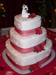 Three tier red and white heart shaped wedding cake decorated with a romantic couple cake top of a bride and groom dancing