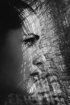 Lady looking thru lace curtain