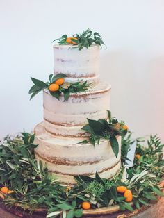 Nearly naked tiered wedding cake with lots of greenery and fruit | Image by Amy Fanton Photography