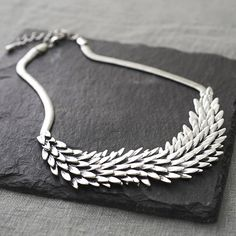 A lovely silver metal necklace with a unique design. A gorgeous detailed feathered effect.