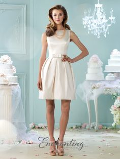 The Enchanting by Mon Cheri 215109 is a short wedding dress, designed with a sleeveless A-line silhouette in rich satin. The princess seamed bodice is capped with a bateau neckline, and tapers through the natural waist with a detachable bow belt. This is complemented with a duo of bow-appliques bands adorning the slightly exposed back. The fully pleated, cocktail-length skirt flares with in-seam pockets and center-back buttons. Available size: 4 to 20.