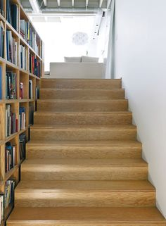 The wide plywood stairs have a built-in bookcase. Behind the stairs is a 5 x 30-foot corridor to store his bigger paintings.