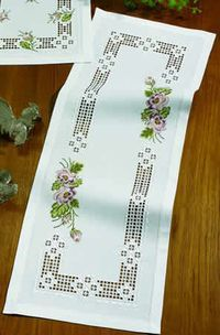 This is a complete Hardanger embroidery with cross-stitched flowers kit from Permin of Copenhagen. The kit contains 22-count white Hardanger fabric, white pearl cotton thread, colored cotton floss, needle, chart, and limited stitch instructions. The finished tablerunner is approximately 15