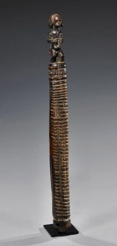 Africa, Gabon, ca. mid 20thCentury.  Wood scraper with a box resonator and a fully-carved figure standing on the end.