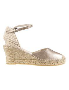 Die Sandalette mit hohem Keilabsatz und verstellbarem Fesselriemchen: eine angesagte Sandalette mit glamouröser Wertigkeit.