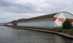 Cartesiusweg 127 - hallen uit 1937-1950 van houthandel RET-Jongeneel aan de 1e Industriehaven. De RET is op de Zeedijk begonnen als Retour Emballage Thee- en rubber kistenfabriek (koloniale retourvracht). RET werd handel in triplex en voor het zachtboard kwam Treetex, deel van Jongeneel. Tot het complex behoort ook Fregatstraat 87-89, een toegang naar dit terrein door een poort met twee bovenwoningen.