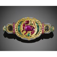 A MUGHAL GOLD INLAID AND GEM-SET JADE BAZUBAND, LATER SET AS A BROOCH BY CARTIER, INDIA, 17TH CENTURY