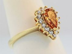 Ring - 14K YELLOW GOLD IMPERIAL TOPAZ AND DIAMOND RING. CENTER SET IS ONE PEAR SHAPED IMPERIAL TOPAZ. TOTAL WEIGHT .94CT. GEM QUALITY. PRONG SET AROUND THE TOPAZ ARE ROUND BRILLIANT CUT DIAMONDS. TOTAL WEIGHT .38CT. G COLOR. VS1 CLARITY. @Jaymark Jewelers #engagment #diamondhalo