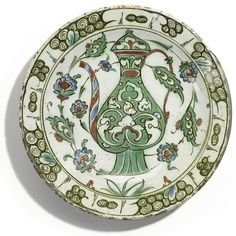 An Iznik polychrome pottery dish with ewer, Turkey, early 17th century - of rounded form with slightly everted rim, painted in underglaze apple green, blue and relief red, outlined in black, with a central ewer decorated with split-arabesques and foliate stems, amidst a scrolling vine of saz leaves and lotus buds, the rim with scrolls, reverse with abstract motifs 26cm. diam.