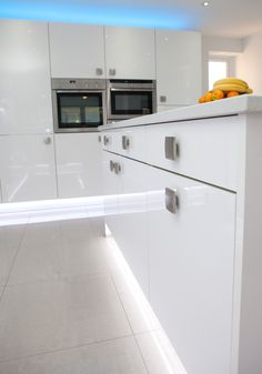 Plinth lighting in this White Gloss Nolte Kitchen with bright blue glass splashbacks and ambient… Plinth Lighting, Kitchen Manufacturers, White Gloss Kitchen, Kitchen Flooring, Glass Splashback, New Homes, Kitchen, Blue Glass, Bespoke Kitchens